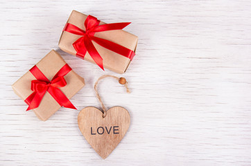 Two little gift boxes with red ribbons and handmade valentine on a white wooden background. Copy space. Valentine's Day.
