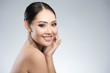 Beauty shot of young pretty asian woman with clear skin ongrey b