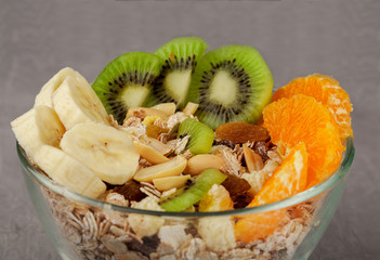 muesli with banana kiwi nuts oranges in a glass bowl