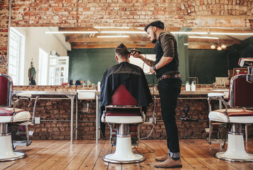 Hairstylist serving client at barber shop
