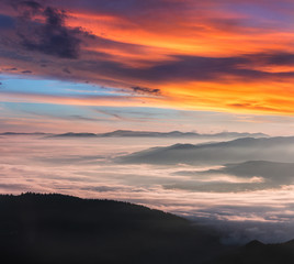 Magical and colorful landscape in the mountains at sunrise. View of foggy hills covered by forest.