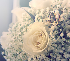 Wedding rings on a bouquet of cream roses