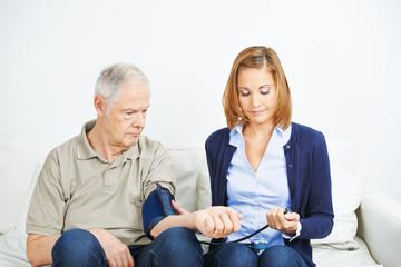 Nursing service doing blood pressure measurement