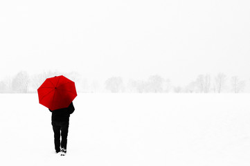 A Woman with a red umbrella in a snowy winter landscape