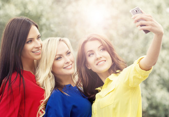 Three beautiful female friends being modern by taking selfies.