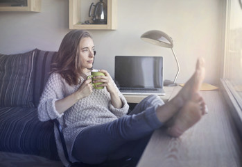 Girl drinking tea with her feet on the table
