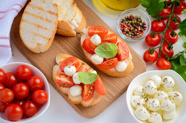 Bruschetta with cherry tomatoes and mozzarella on wooden board, top view