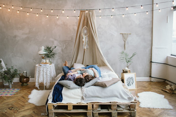 Young hipster couple having fun on handmade bed with dreamcatche