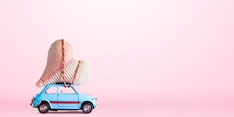 Blue retro toy car delivering craft heart for Valentine's day on pink background