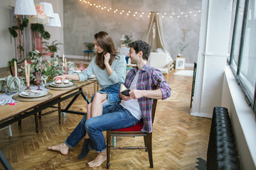 Young happy hipster couple enjoying meal in rustic old loft