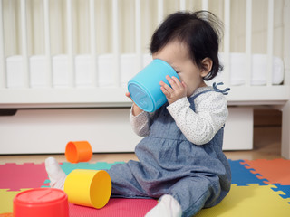 Baby girl playing stack cups at home
