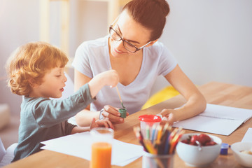 Happy mother drawing together with her son