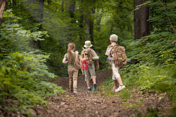 boys and girl on camping trip in the forest exploring