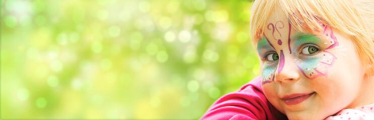 glückliches geschminktes Mädchen in einem Freizeitpark blickt in die Kamera