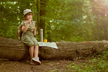 excited child on  camping trip in green forest