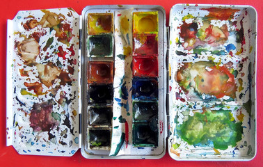 Watercolor paint box on red table