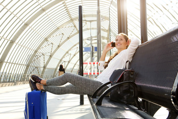 happy woman sitting on bench talking on mobile phone