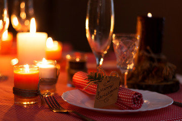 Festive composition with candles and plates. Table decoration. A beautiful table setting, red table cloth, tablecloth in a cage. Christmas dinner. A white plate with a nice napkin on the tabl