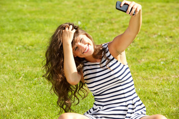 young happy woman taking selfie outside
