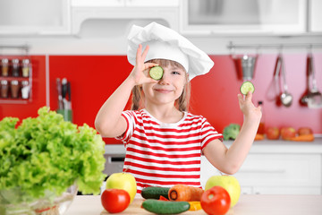 Small girl playing with vegetables in kitchen