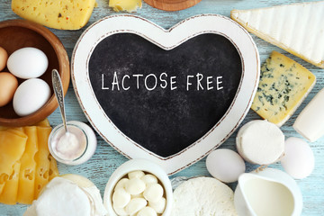 Fotobehang Zuivelproducten Allergic food concept. Dairy products and heart shaped board with text LACTOSE FREE on table