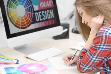 Beautiful young designer working in office