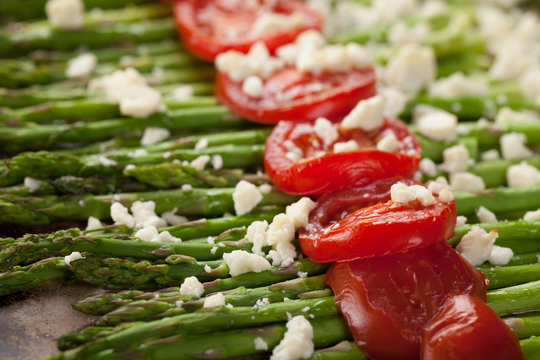 Roasted Asparagus topped with Campari tomatoes, Feta Cheese, Olive oil, and salt macro shot