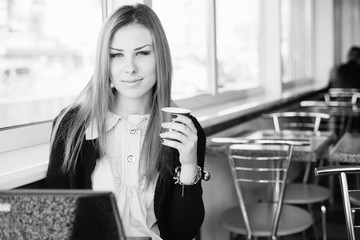 Business woman in restaurant or coffee shop using working on laptop computer, light window background