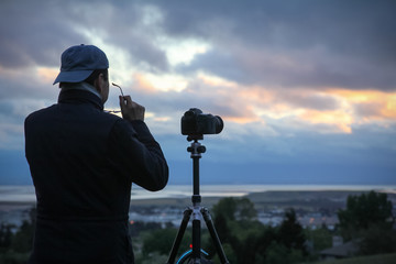 Man composes a photo at sunset in the east bay area looking west