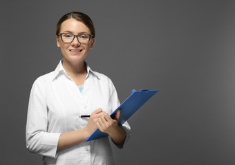 Young doctor with clipboard on grey background