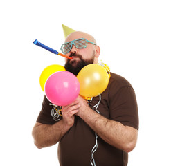 Funny fat man with party blower and colorful balloons on white background