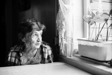 An elderly woman sadly looking out the window. Black-and-white photo.