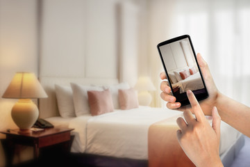 Woman hands using mobile phone take photo at hotel room blurred background