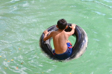 Boy with inner tubing at Blue Lagoon,Vang Vieng.Vientiane Province,Laos.