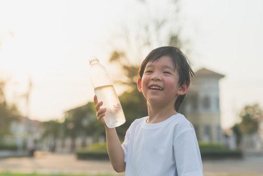 sian boy drinks water from a bottle