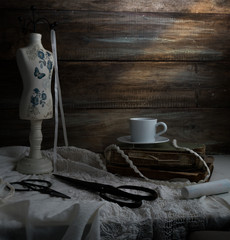 still-life with a cup of coffee, scissors, mannequin sewing and lace on a background of rough wooden walls. vintage