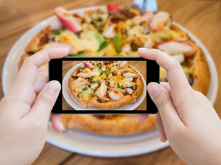 woman taking photo of Pizza with mobile smartphone