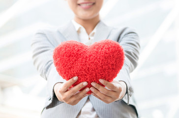 Close up of happy Asian female hands holding red heart and blurred on woman's smiling face with city and building background. Valentines Day, love or working girl and good health concept.