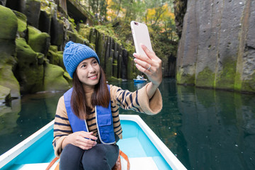 Woman taking selfie in Takachiho Gorge
