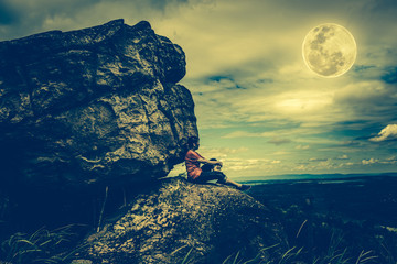 Woman sitting on boulders, sky with cloudy and full moon. Low key picture style.