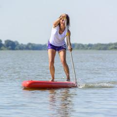 kraftvolles Workout beim Stehpaddeln auf dem See