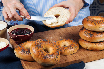 Hands spread cream cheese Fresh homemade Poppy bagels bread on w