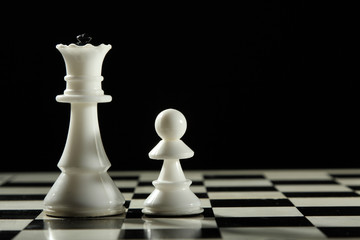 Two  white chess pieces on the board on a dark background.