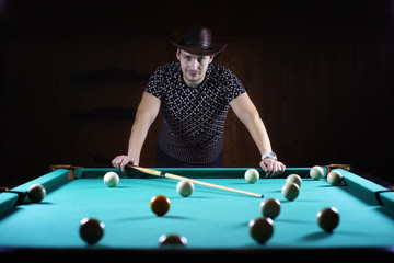 hansome man playing billiards alone