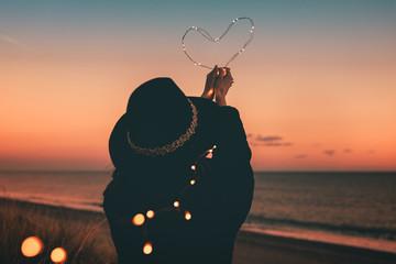 San Valentino. Cuore luminoso tenuto in mano da una ragazza vestita di nera sulla spiaggia al tramonto.