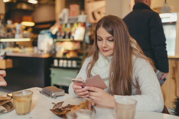 beautiful girl drinking coffee and texting on smart phone in cafe