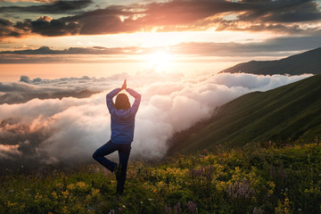 woman in the mountains during a foggy dawn exercise in yoga