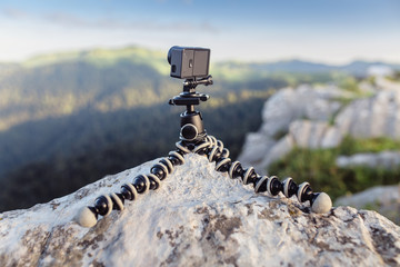 Action camera mounted on a tripod gorilla with summer mountains in the background