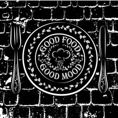 Black and white vector illustration of a plate, fork and knife and the words GOOD FOOD GOOD MOOD