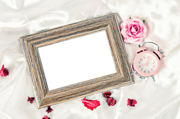 Blank wooden photo frame and pink alarm clock with rose.